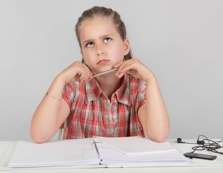 Portrait of young pensive elementary school girl making homework and intensively looking up with a wondering facial expression as if looking for a solution for a difficult task. Zdjęcie Seryjne