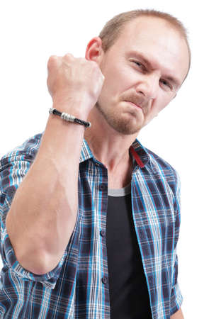insulting: Angry man with clenched lips with an expression of rage showing his arm and fist up as a threatening insult. Isolated over white. Focus on eyes but wide DOF. Stock Photo