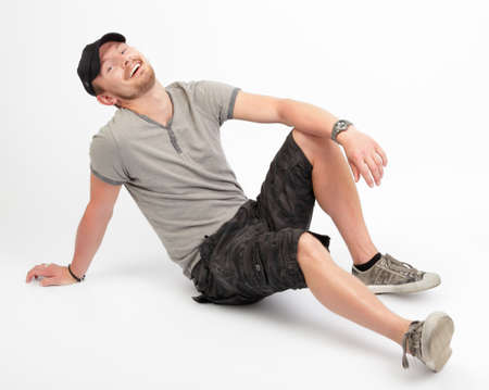Young Caucasian dude sitting on floor wearing cap and in casual urban outfit leaning backwards with a big smile. Full body shot. White background but not isolated.