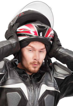 Closeup portrait of young bearded macho motorcycle or bike rider pulling a helmet off his head with a tough expression of effort. Isolated over white. photo
