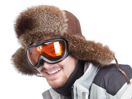 Cropped happy skier portrait of a bearded you man wearing sunglasses and a fur bearskin hat, leaning forward ready for action. Isolated over white.