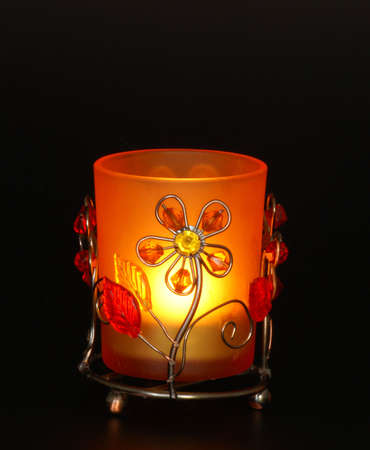 christmas perfume: fire, light of candle, black background