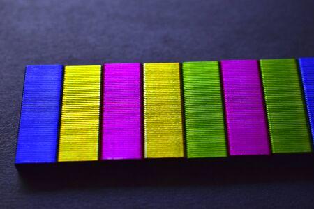 Multi-colored stapler staples on a black background 版權商用圖片
