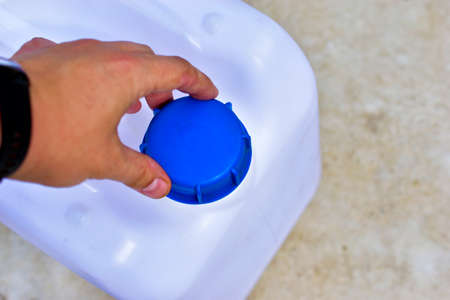 A white plastic canister with a blue lid in the hands of a man