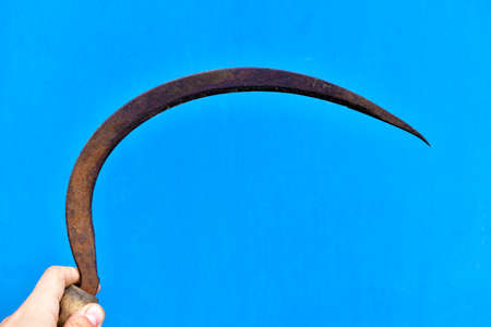 Iron sickle in hand on a blue background