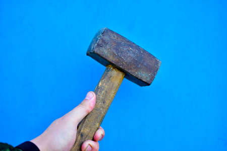 Small sledgehammer in hand on a blue background