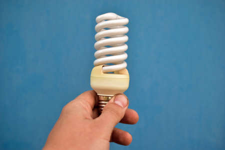 Twisted fluorescent lamp in hand on a blue background