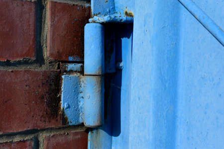 Hinged iron hinges on garage doors in blue