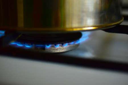 Shiny teapot on a gas burner on the stove