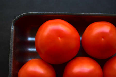Red ripe tomatoes in a package on a black background