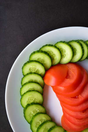 Sliced Green cucumber and tomato on a white plate on a black background