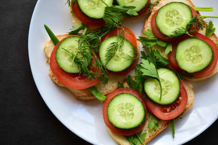 Diet sandwiches with greens, cucumber and tomato on a white plate