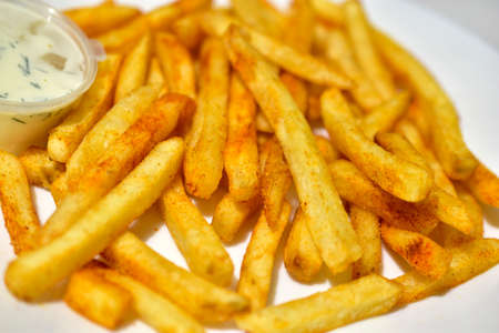 Bright yellow French fries on a white plate with sauce