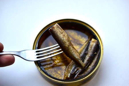 Sprats in oil in a jar with a fork on a white background