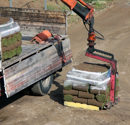 turf pile: Unloading Rolls of turf stacked on top of each other Stock Photo