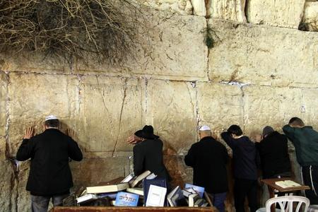 Unidentified orthodox jewish men are praying at Western wall