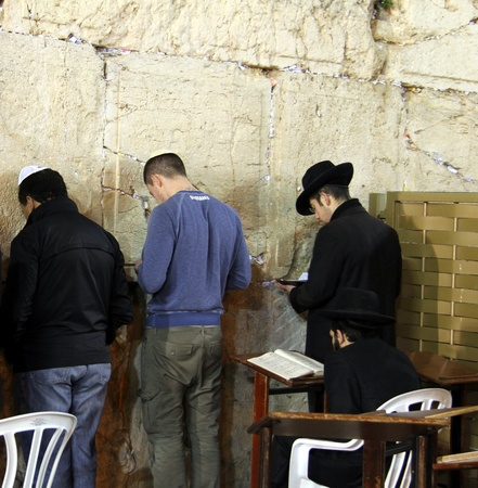 Unidentified jewish men are praying at Western wall photo