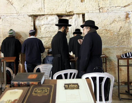 Unidentified orthodox jewish men are praying at Western wall , an important jewish religious site