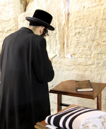 unidentified: Unidentified orthodox jewish man prays at Western wall , an important jewish religious site