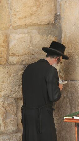 Unidentified orthodox jewish man prays at Western wall , an important jewish religious site  photo