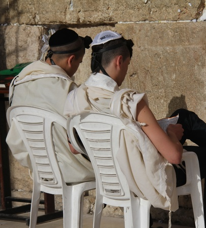 Unidentified  young people in tefillins are praying at the Wailing wall  Western wall  photo