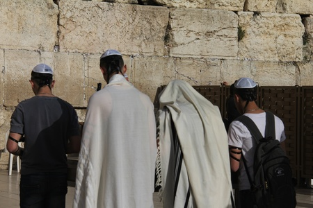 Unidentified  young people in tefillins are praying at the Wailing wall  Western wall