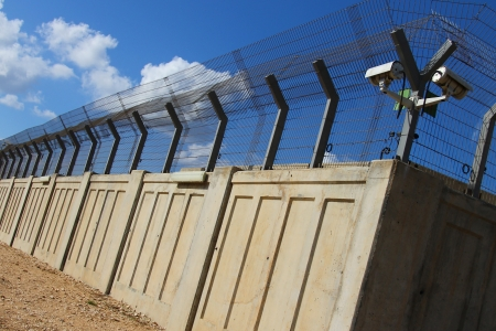 A secured industrial zone with concrete fence on the blue sky background