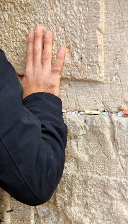 orison: Hand of praying man on the Western Wall  in Jerusalem Stock Photo