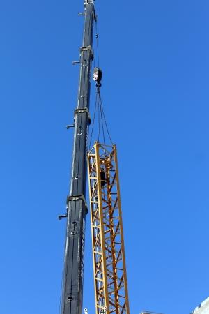 dismantling: TEL AVIV , ISRAEL - FEBRUARY  18  Tower crane dismantling on blue sky background in Tel Aviv, Israel on February  18, 2013 Editorial