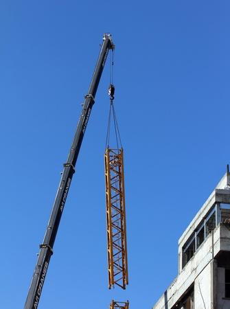 TEL AVIV , ISRAEL - FEBRUARY  18  Tower crane dismantling on blue sky background in Tel Aviv, Israel on February  18, 2013 Stock Photo - 18170584