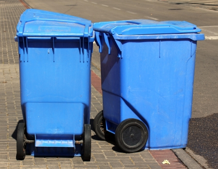 Blue garbage cans on  the sidewalk photo