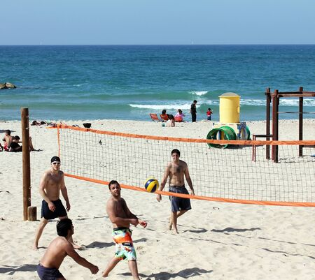 TEL AVIV , ISRAEL – MARCH 19: Group of young people playing volleyball on the beach of Tel Baruch on March 19, 2013 in Tel Aviv. Beach volleyball favorite game Israelis on vacation.