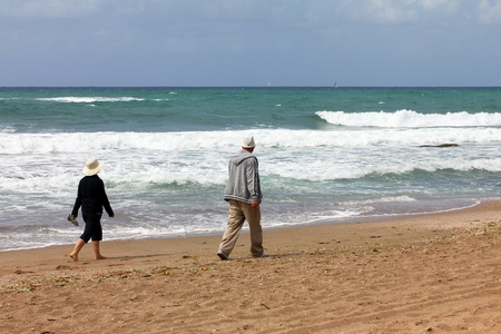 Quarreled couple of elderly people walking separately on the beach photo