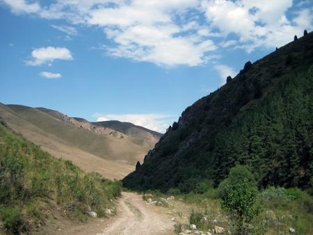 remoteness: Mountainous summer landscape of Kyrgyzstan with road in foreground