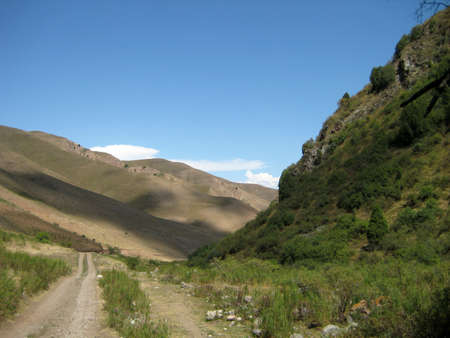 remoteness: Mountainous summer  landscape of Kyrgyzstan with road in foreground Stock Photo