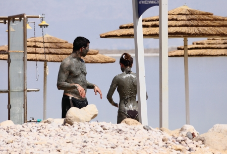 NEVE ZOAR, ISRAEL – MAY 24: Young caucasian  couple taking mud treatment outdoor on summer day on May 24, 2013 in Neve Zoar, Israel.