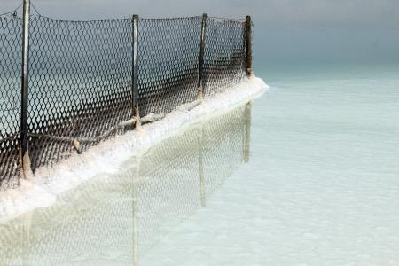 gradually: Dead sea. Metal mesh fence gradually becomes covered with salt Stock Photo