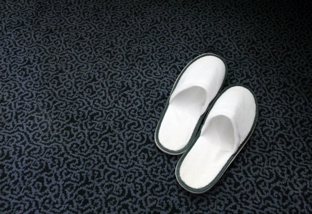White hotel spa slippers on the dark carpet Stock Photo - 20054332