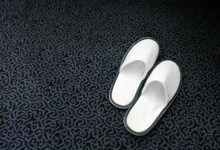White hotel spa slippers on the dark carpet Stock Photo - 20054332