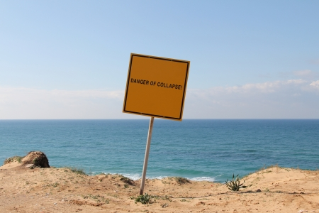unstable:  Dandger of collapse  A sign on the edge of a hill overlooking the sea  The sign warns  Danger, Stay Back, Unstable Cliffs,  Keep Out Stock Photo