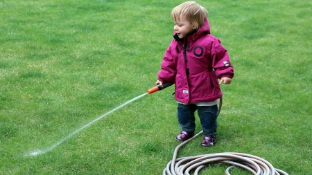 Little girl  one year and 6 months  watering grass lawn in the yard with a hose photo