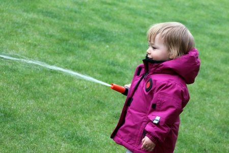 Little girl  one year and 6 months old  watering grass lawn in the yard with a hose photo