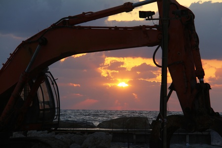 Large excavator on the sunset  over sea background photo