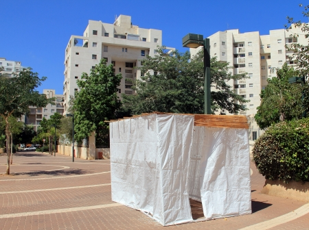 hebrews: A sukkah is a temporary hut constructed for use during the week-long Jewish festival of Sukkot. It is topped with branches and often well decorated with autumnal, harvest or Judaic themes. Stock Photo