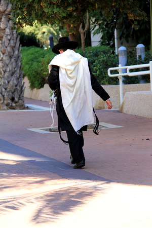A religious Jew in the praying  traditional robe walking down the street