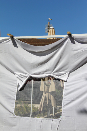 tabernacles: A sukkah is a temporary hut constructed for use during the week-long Jewish festival of Sukkot. It is topped with branches and often well decorated