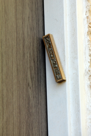 Modern Mezuzah - Jewish symbol, on an old door