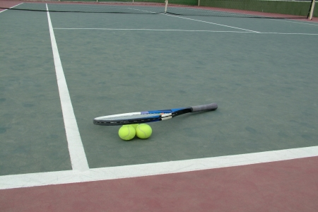 Tennis racket lying on a tennis ball near the net and court line photo
