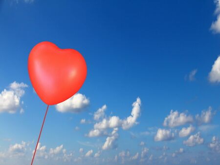 Red heart like balloon on blue cloudy sky  photo