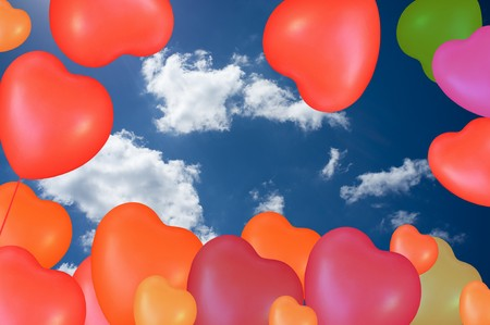 Different colored hearts like balloons on blue cloudy sky  photo